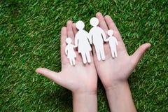 Menschliche Hände, die Papierschnitt der Familie halten Stockfotos