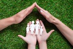 Menschliche Hände, die Papierschnitt der Familie halten Stockfoto