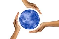 Menschliche Hände, die Planetenerde abdecken. Lizenzfreies Stockbild
