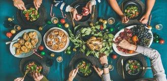 Menschliche Hände, die verschiedene Mahlzeiten am Weihnachtsfestabendessen essen lizenzfreie stockfotografie