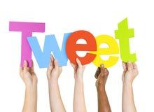 Menschliche Hände, die Wort-Tweet halten Stockfotografie