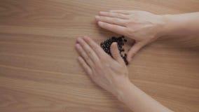 Menschliche Hände häufen oben schwarze Bohnen auf Holztisch an stock footage