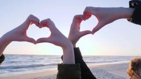 Menschliche Hände machen Herz gegen Himmel bei Sonnenuntergang auf Seeküste stock video