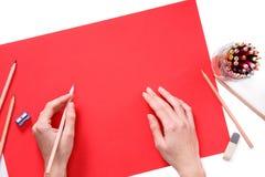 Menschliche Hände mit Bleistift-Zeichnung etwas auf dem roten Papier lokalisiert auf weißem Hintergrund Stockfoto