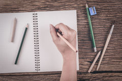 Menschliche Hände mit Bleistiftschreiben auf Papier auf Holztisch Lizenzfreies Stockfoto