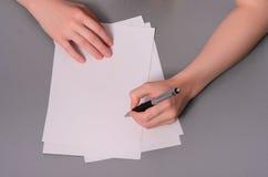 Menschliche Hände mit Bleistiftschreiben auf Papier und Löschengummi auf Holztischhintergrund Stockfotos
