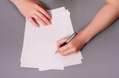 Menschliche Hände mit Bleistiftschreiben auf Papier und Löschengummi auf Holztischhintergrund Stockbild