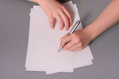 Menschliche Hände mit Bleistiftschreiben auf Papier und Löschengummi auf Holztischhintergrund Stockbilder