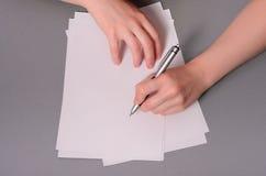 Menschliche Hände mit Bleistiftschreiben auf Papier und Löschengummi auf Holztischhintergrund Stockfotografie