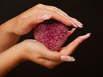 Menschliche Hände mit Maniküre halten rosafarbenes Inneres an Stockfotos