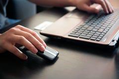 Menschliche Hand auf Computermaus. Stockfotos