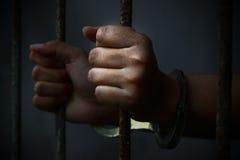 Menschliche Hand des Gefangenen auf Stahlgitter Stockfoto