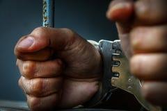 Menschliche Hand des Gefangenen auf Stahlgitter Stockbild