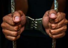 Menschliche Hand des Gefangenen auf Stahlgitter Lizenzfreie Stockfotografie