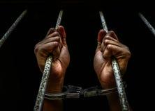 Menschliche Hand des Gefangenen auf Stahlgitter Lizenzfreie Stockfotos