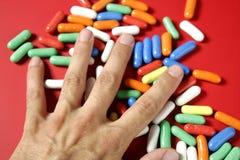 Menschliche Hand, die bunte Süßigkeit anhält Lizenzfreie Stockfotos