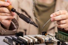 Menschliche Hand, die den Lötkolben repariert Computer boad hält Stockfotografie