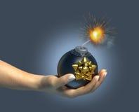 Menschliche Hand, die eine typische Bombe/ein Geschenk anhält. Lizenzfreie Stockbilder
