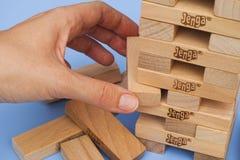 Menschliche Hand, die einen Block von Jenga-Turm entfernt Stockfotografie