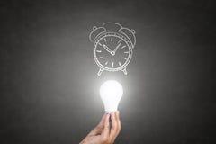 Menschliche Hand, die Glühlampe mit Uhr hält Lizenzfreies Stockfoto