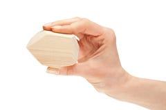 Menschliche Hand, die hölzernen Block anhält Stockfotografie