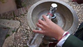 Menschliche Hand, die herauf die aufbereitete Flasche mit Wasser vom allgemeinen typischen Wasserbrunnen in Granada füllt stock footage