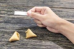 Menschliche Hand, die leeres Papier für Zitat oder Mitteilung von den Glückskeksen blockiert stockbilder