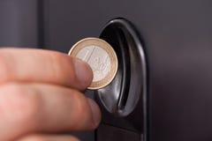 Menschliche Hand, die Münze einfügt Lizenzfreie Stockfotos