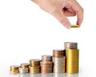 menschliche Hand, die Münze zum Geld setzt Lizenzfreie Stockfotografie