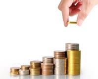 menschliche Hand, die Münze zum Geld setzt Lizenzfreie Stockfotos