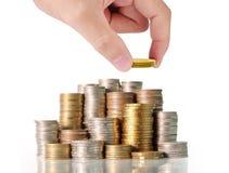 menschliche Hand, die Münze zum Geld setzt Stockfoto