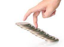 menschliche Hand, die Münze zum Geld setzt Stockfotografie