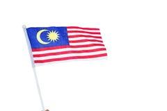 Menschliche Hand, die malaysische Flagge hält Lizenzfreie Stockfotografie