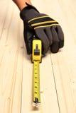 Menschliche Hand, die Messen auf einem Block des Holzes nimmt Stockfotos