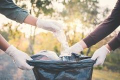 Menschliche Hand, die Plastik in Behältertasche auf Park, freiwillige Co aufhebt lizenzfreie stockfotos