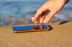 Menschliche Hand, die wasserdichtes intelligentes Telefon auf dem Sand nimmt lizenzfreie stockfotografie