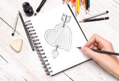 Menschliche Hand mit Bleistift zeichnet in Notizbuch Stockbild