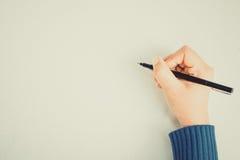 Menschliche Hand mit Bleistiftschreiben etwas Stockfotografie