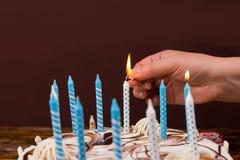 Menschliche Hand mit dem Matchstick, eine Kerze auf einem Geburtstagskuchen beleuchtend Stockfotos