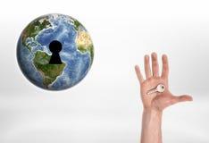 Menschliche Hand mit dem Schlüssel von Planet Erde Lizenzfreie Stockbilder