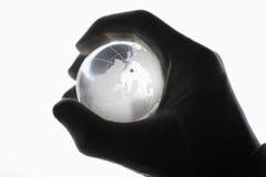 Menschliche Hand mit den Baumwollhandschuhen, die Glaskugel greifen Lizenzfreies Stockbild