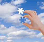 Menschliche Hand mit letztem Puzzlespielstück Lizenzfreies Stockfoto