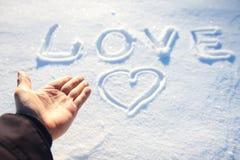 Menschliche Hand und das Wort lieben im Schnee Lizenzfreie Stockfotografie