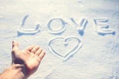 Menschliche Hand und das Wort lieben im Schnee Lizenzfreie Stockbilder