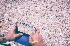 Menschliche Hand unter Verwendung des intelligenten Telefons nehmen Muscheln eines Fotos Lizenzfreies Stockfoto