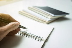 Menschliche Handschrift der Nahaufnahme etwas auf Papiernotizbuch im sunli Lizenzfreie Stockfotografie