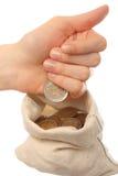 Menschliche Handwerfende Münzen in einen Sack Stockbild