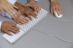 Menschliche Hände auf Computertastatur mit einer Hand unter Verwendung der Computermaus Stockfotografie