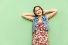 Menschliche positive Gefühle Das schöne langhaarige blonde Mädchen im Kleid, Spaß habend, kreuzte Hand-onder Kopf Stockbilder
