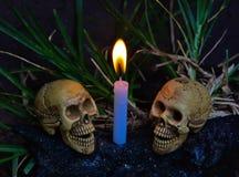 Menschliche Schädel mit Kerzenlicht-Dunkelheitshintergrund Stockbilder